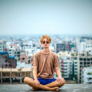 Man meditating cross legged with cityscape behind