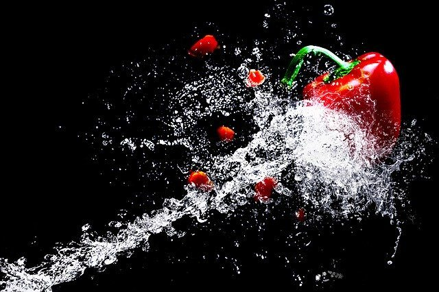 Red pepper being lifted by a jet of water