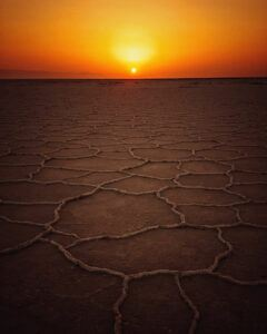 Dry and barren earth with sunset on horizon