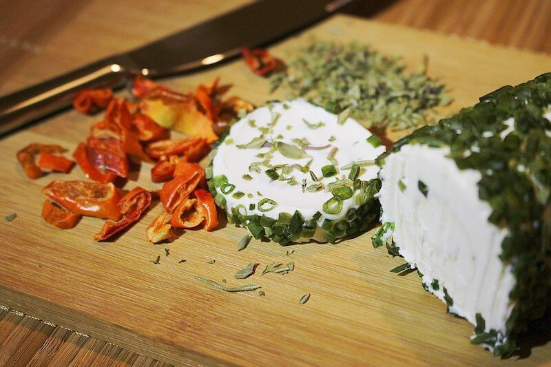 Roll of herb cheese on chopping board