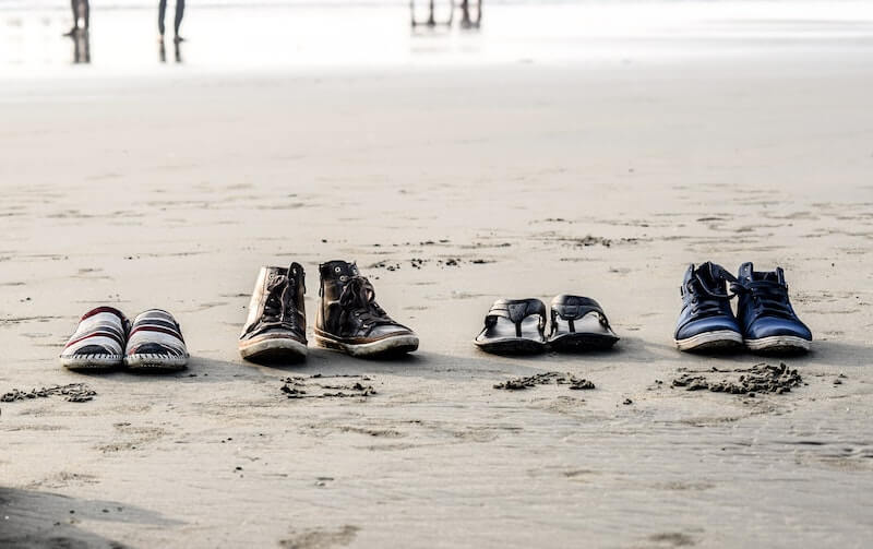 Four pairs of shoes lined up on beach