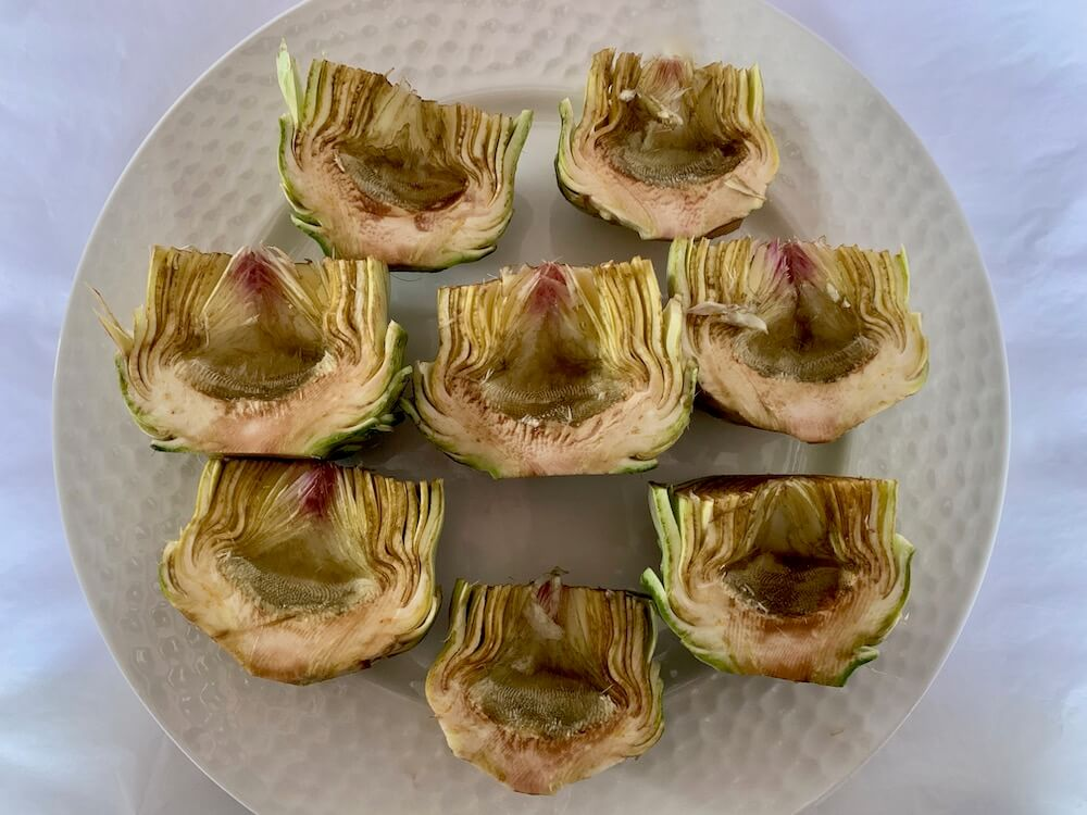 Plate of prepared artichokes, ready for cooking