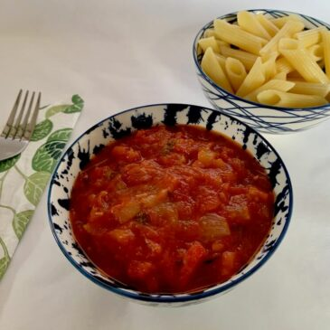 Bowl of tomato sauce with a bowl of pasta in the background