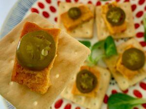 Slice of cashew cheese with jalapeño on gluten free cracker