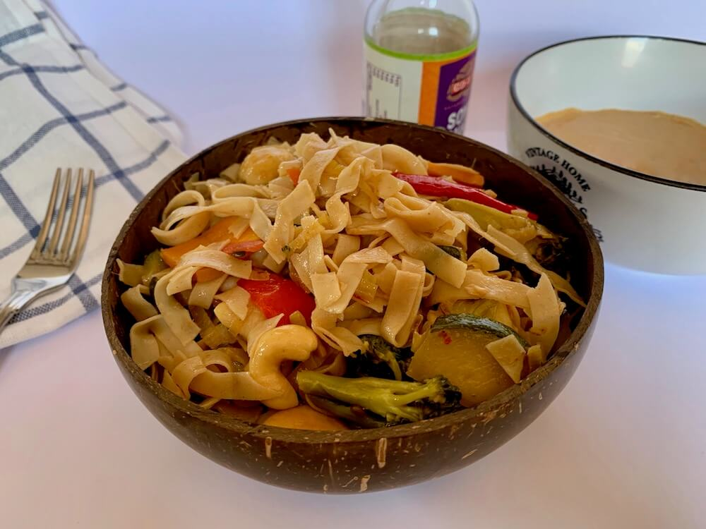 Bowl of gluten free noodles with vegetables and spicy peanut sauce