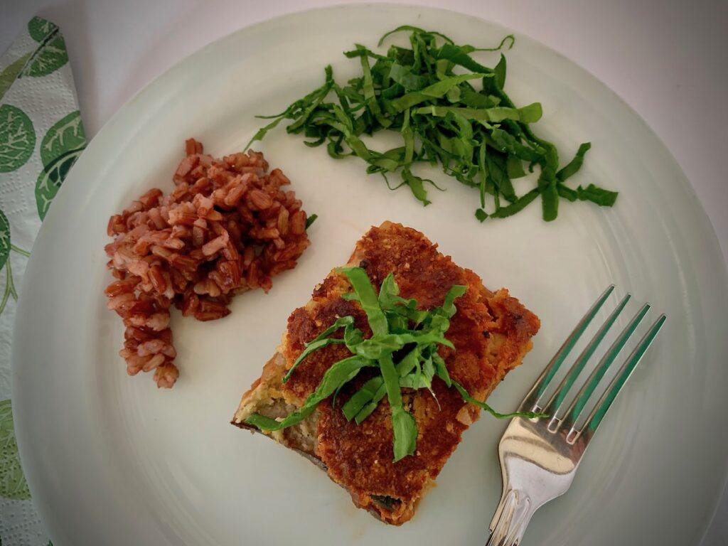 Slice of vegan eggplant parmesan and red rice