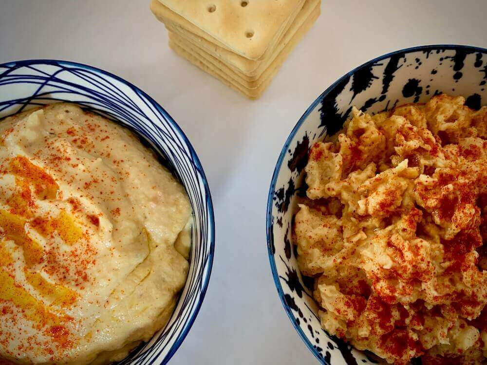 Two bowls of hummus, one smooth and one chunky