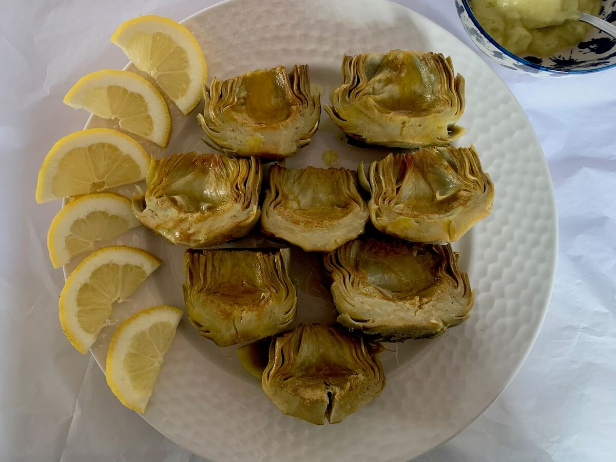 Plate of cooked artichokes with lemon slices