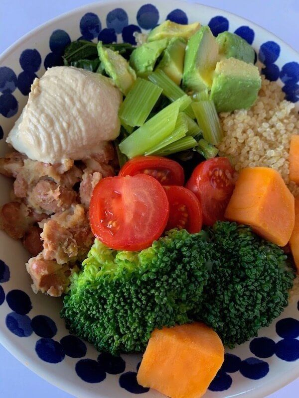 Vegan buddha bowl with quinoa, refried beans, broccoli and sweet potato