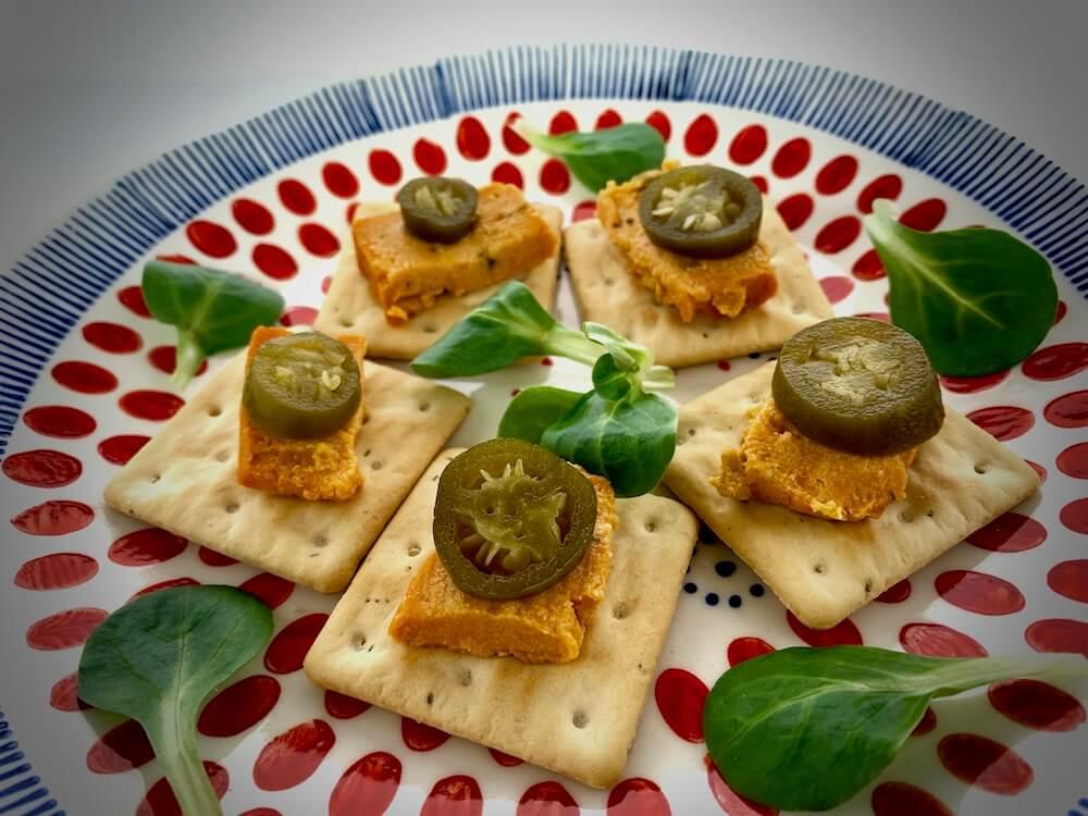 Vegan cheese with jalapeños on gluten free crackers