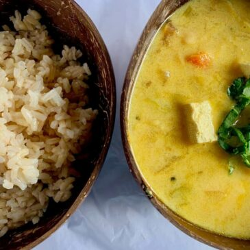 Two half bowls, one with rice, one with vegan coconut curry