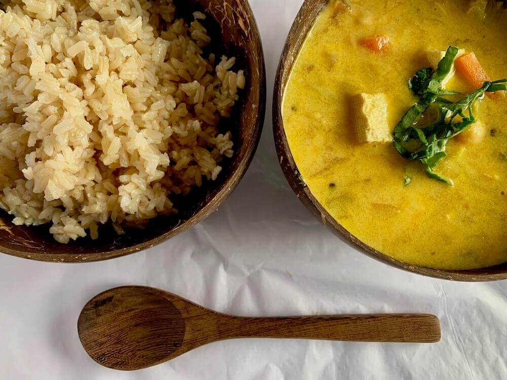 A bowl of rice and a bowl of vegan coconut curry
