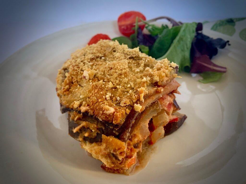 Slice of vegan eggplant parmesan with garnish