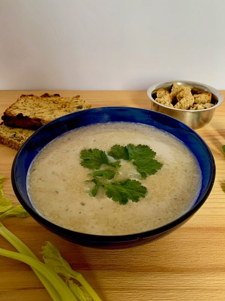 Blue bowl of celery soup with garnish of coriander leaves and gluten free croutons