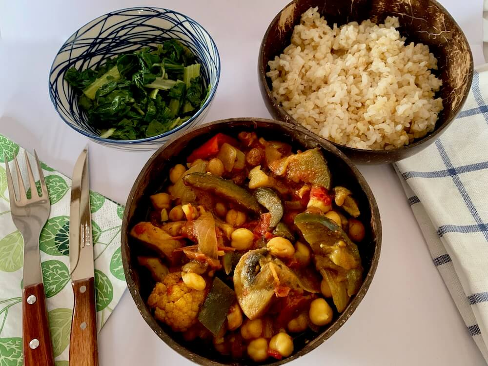 Bowl of eggplant curry with rice and spinach