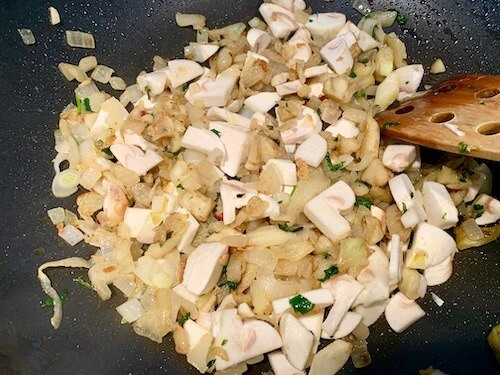 Onions, eggplant and mushrooms in a frying pan