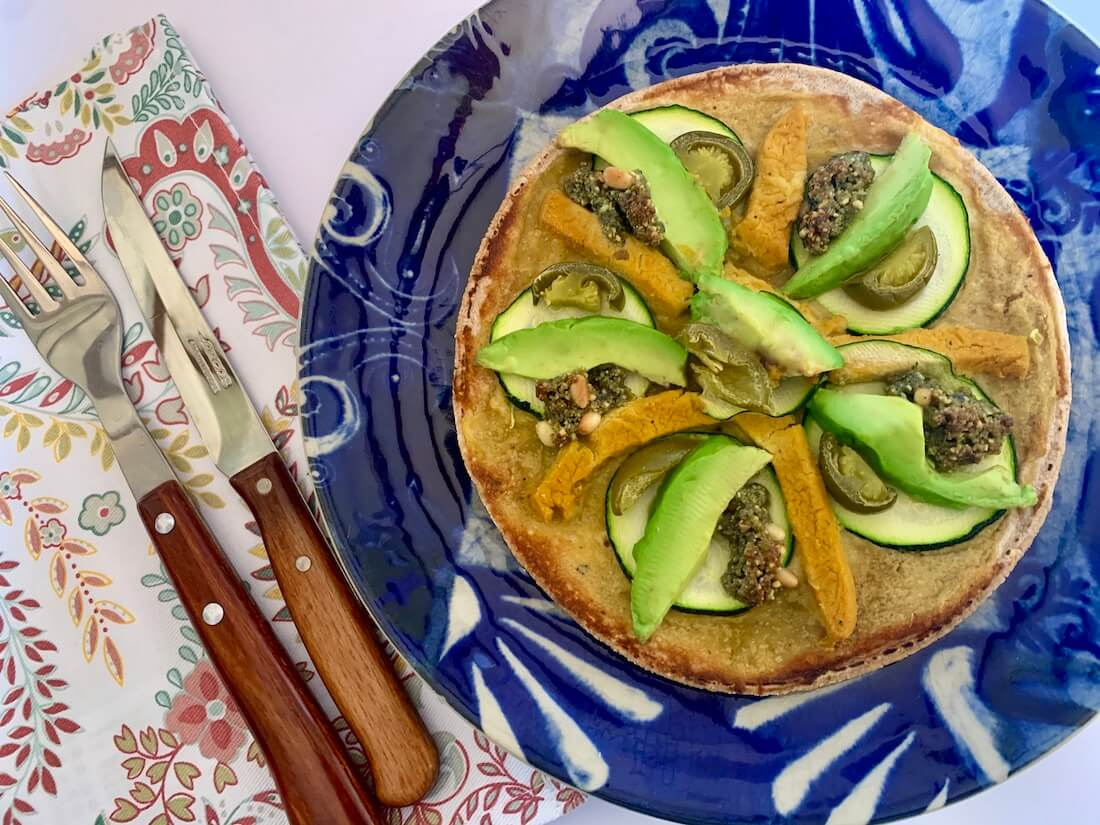 Gluten free vegan pizza with avocado on top