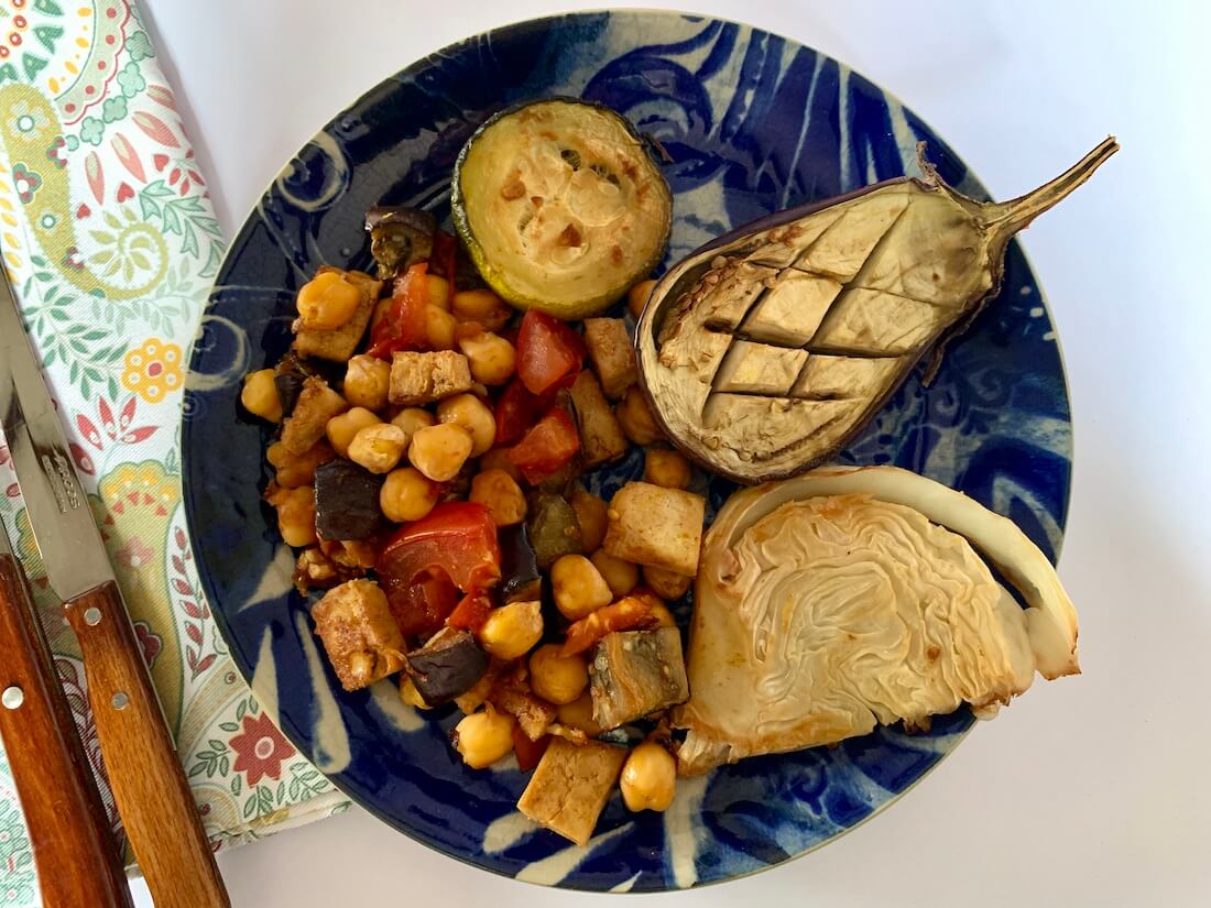 Plate with roasted eggplant, cabbage, zucchini and chickpea mix