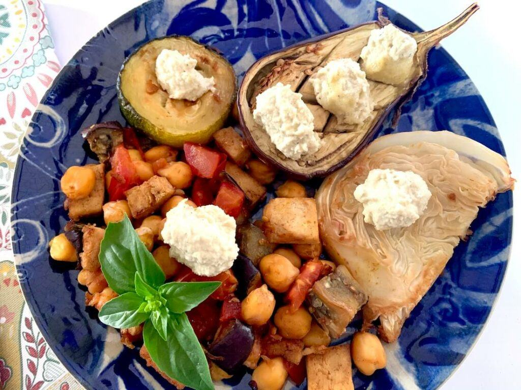 Plate with roasted eggplant, cabbage, zucchini and chickpea mix, topped with cashew nut sauce