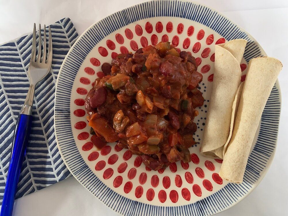 Plate of vegan chilli beans with gluten free wraps