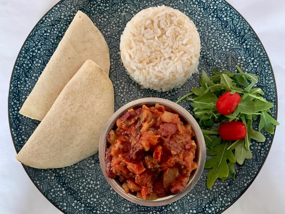 Blue plate with gluten free wraps, rice and vegan chilli beans