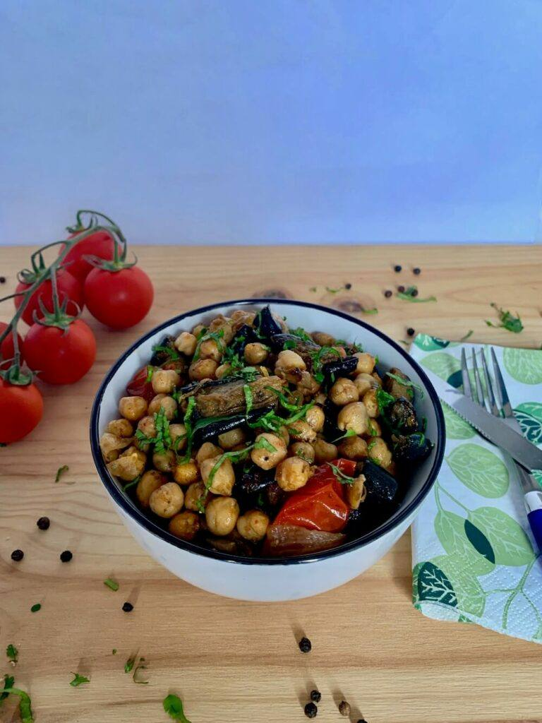 Bowl of roasted chickpeas with eggplant and cherry tomatoes