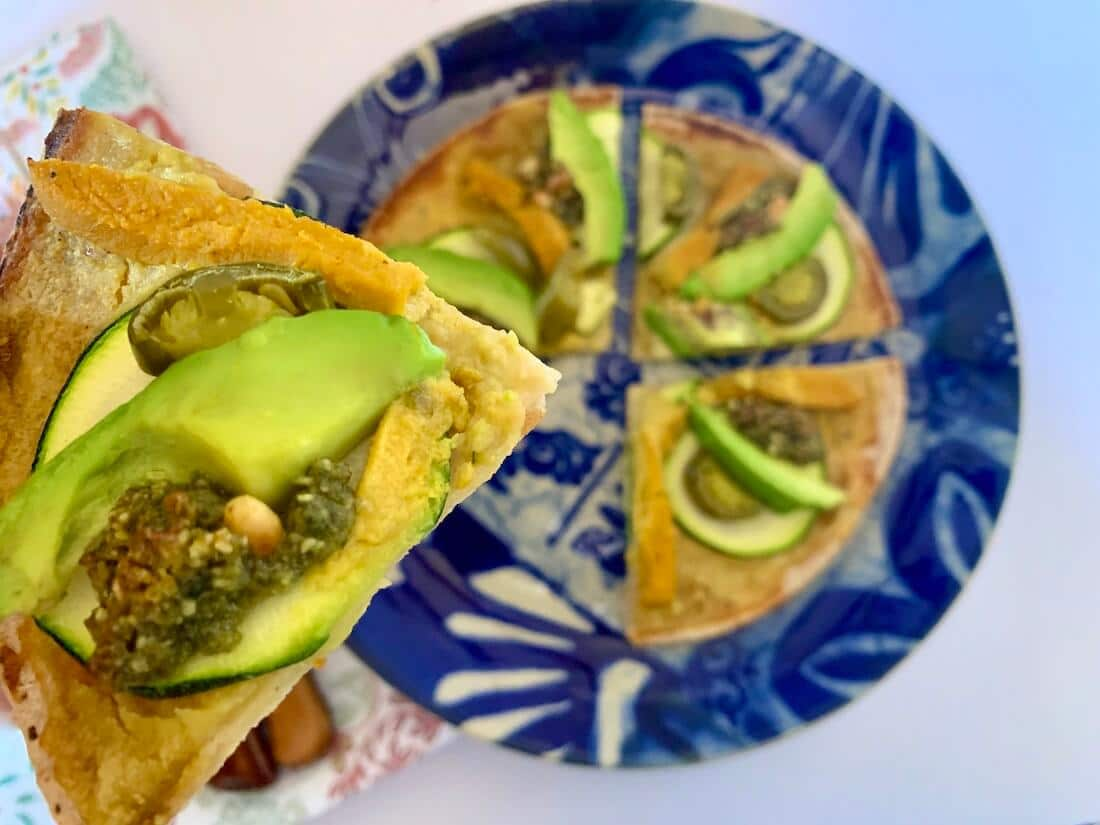 Slice of gluten free vegan pizza with avocado on top