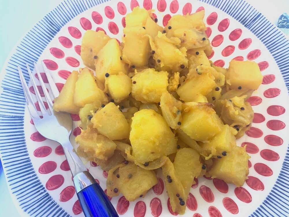 Potatoes cooked in turmeric and black mustard seeds