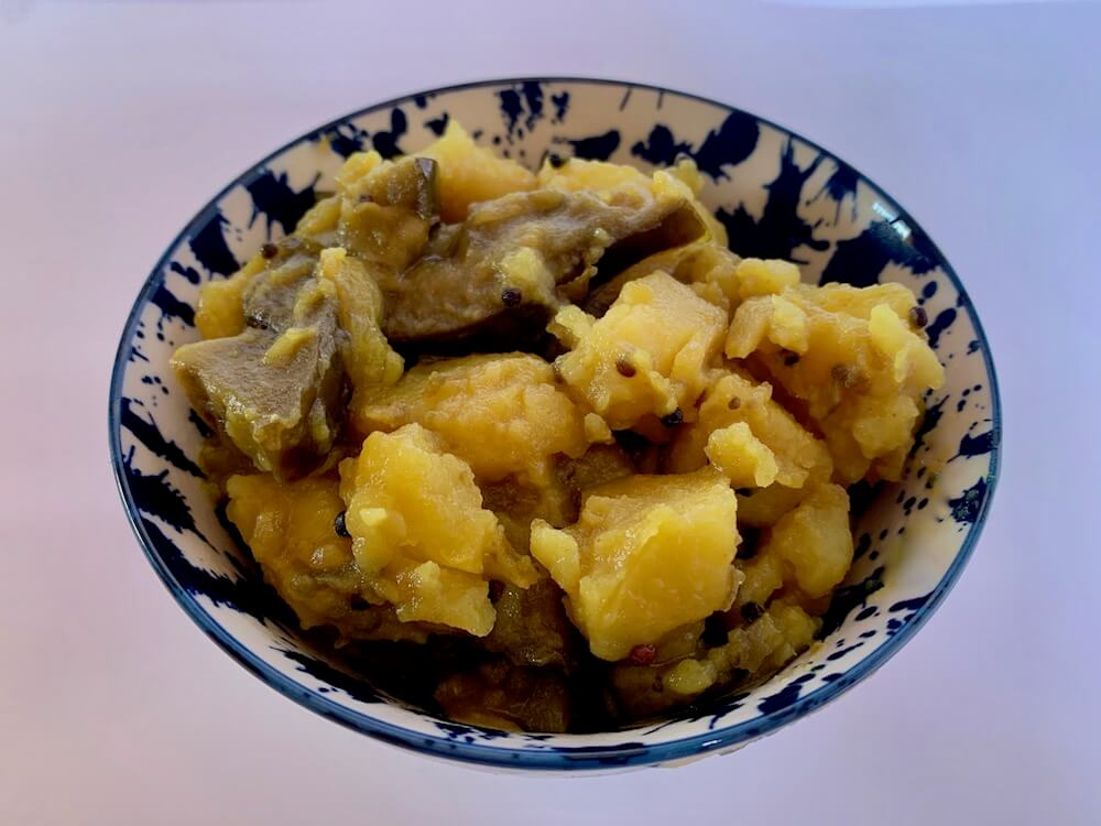 Bowl of potatoes and eggplant cooked in turmeric