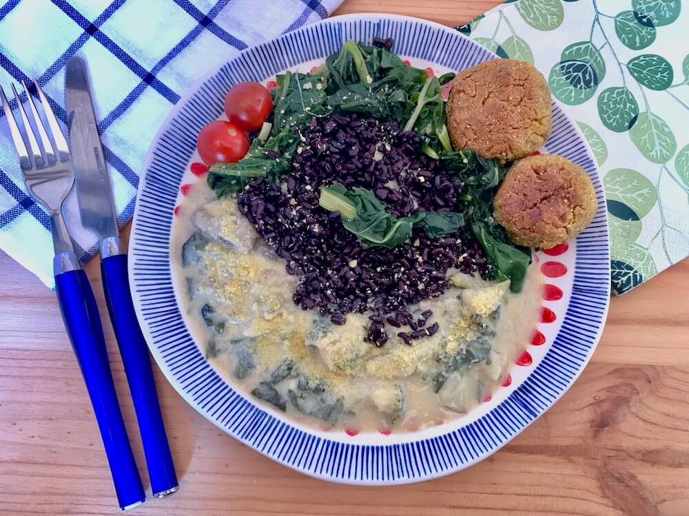 Plate with black rice, vegan creamy cheese sauce, spinach and vegan croquette balls