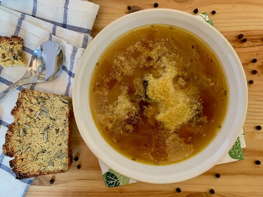 Bowl of vegan french onion soup with gluten free bread and nutritional yeast