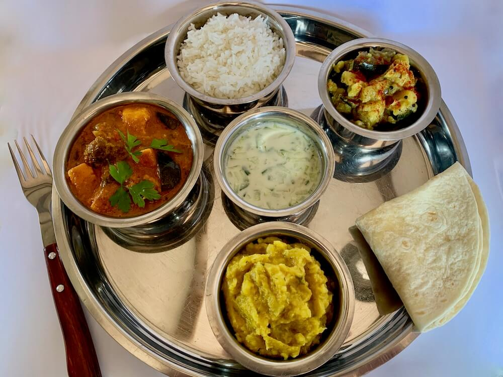 Vegan thali platter with rice, turmeric potatoes, dahl, sweet potato curry and gluten free flatbread