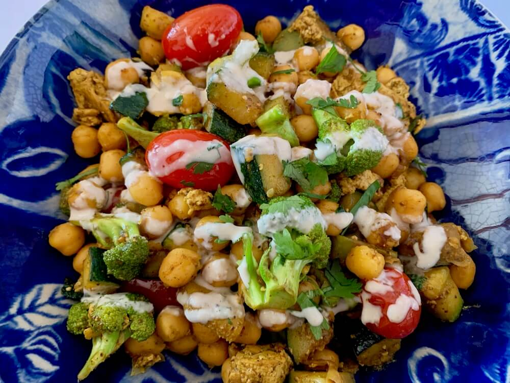 Bowl of quick chickpea recipe with broccoli & zucchini drizzled with tahini sauce