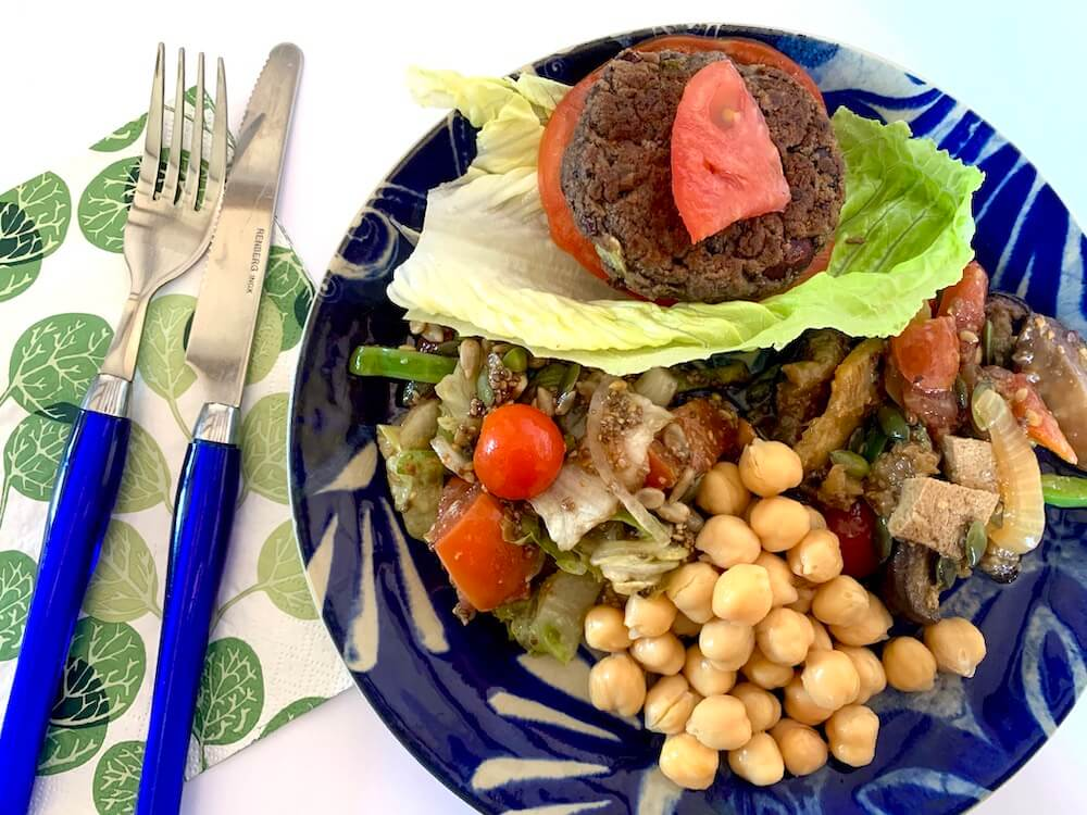 Easy vegan bean burger on a plate with salad, grilled veggies and chickpeas