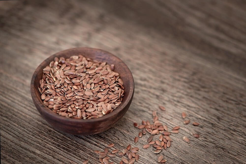 Bowl of flax seed on wooden table