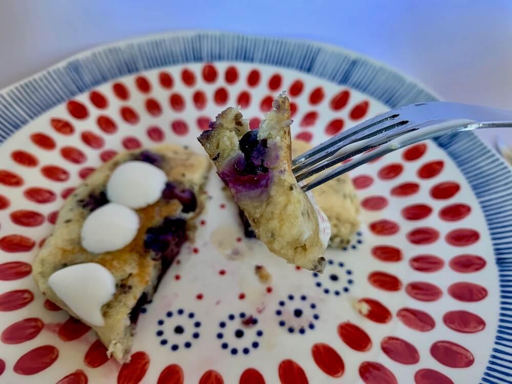 Piece of blueberry pancake with vegan cream on top
