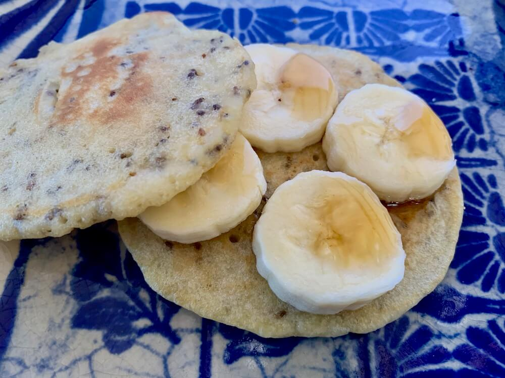Vegan gluten free pancake with banana and maple syrup on top