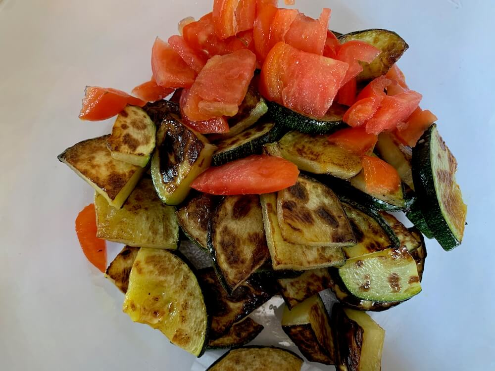 Grilled zucchini slices with raw tomato