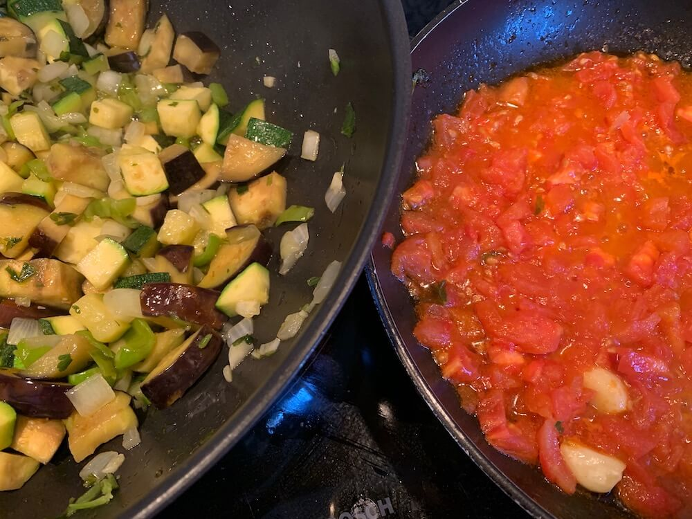 One pan with pisto vegetables and one pan with frying tomatoes