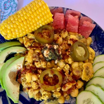 Blue plate with tofu scramble, avocado slices, tomato & cucumber