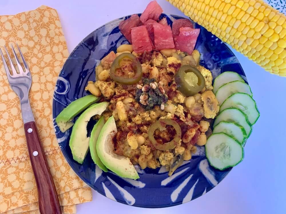 Blue plate with tofu scramble, avocado slices, tomato & cucumber