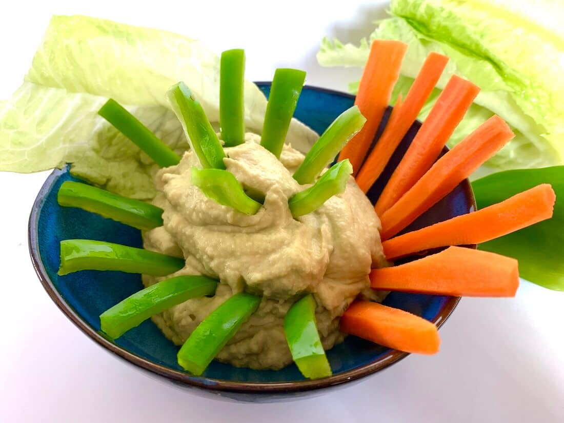 Bowl of avocado dip with crudités of green pepper and carrot sticking into it