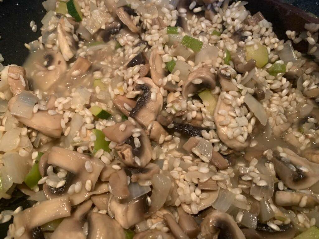 Raw rice added to the pan of mushrooms and onions
