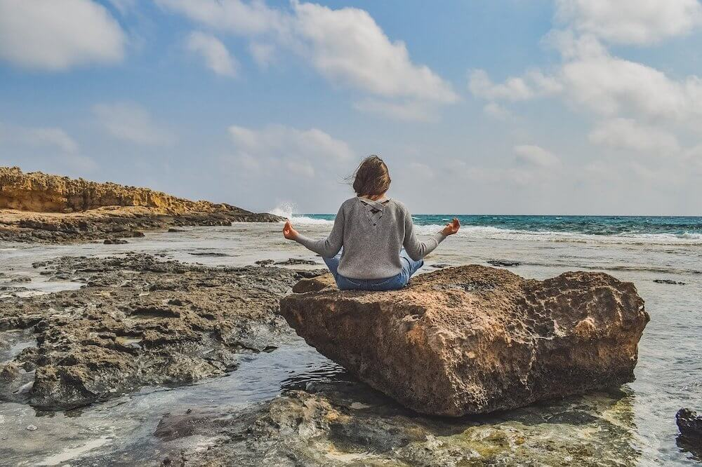 Girl sitting on a rock on the beach doing yoga