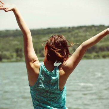 Woman facing away from camera with arms up in air in happiness