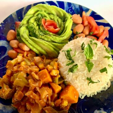 Plate of oil free stir fry in tomato, rice & an avocado rose
