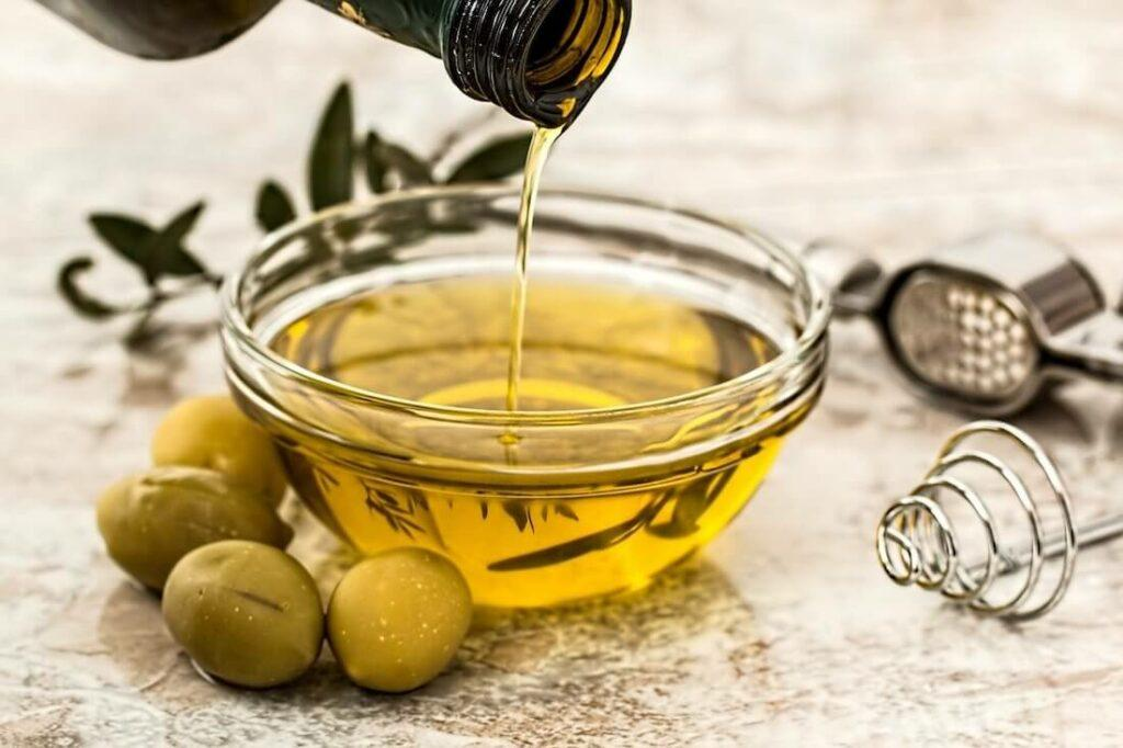 Bowl of olive oil with olives next to it