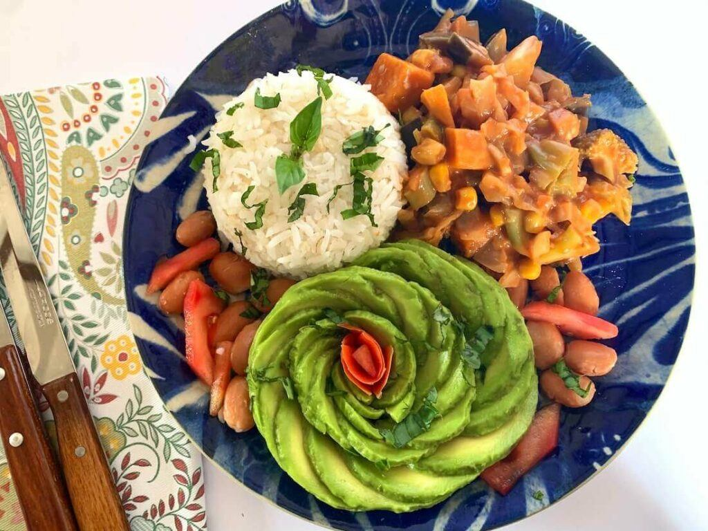 Plate of veggies with rice and an avocado rose