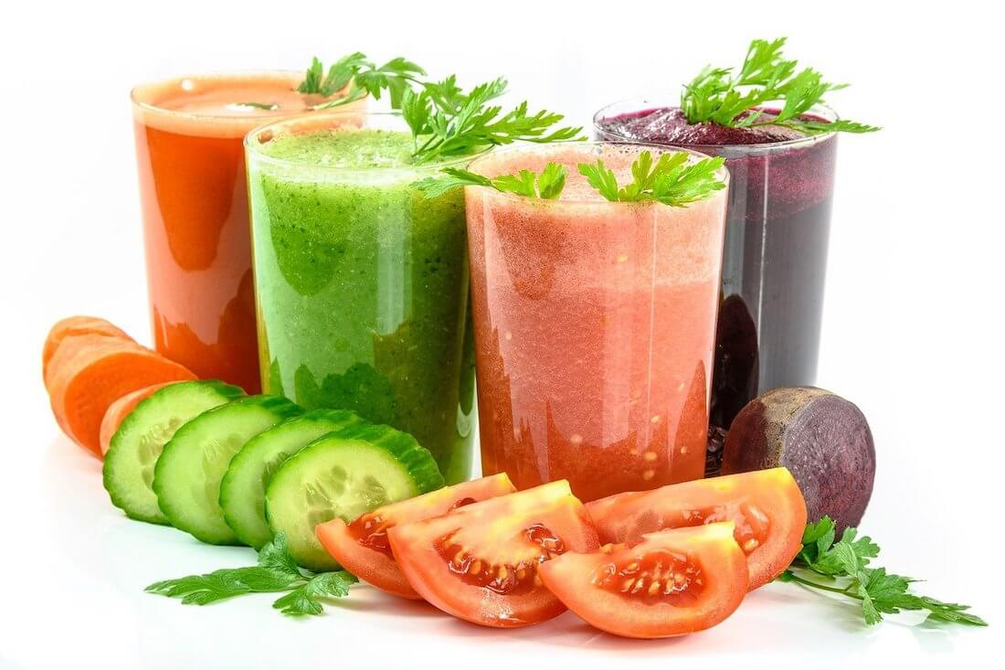 Four different coloured vegetable juices, two red, one purple and one green