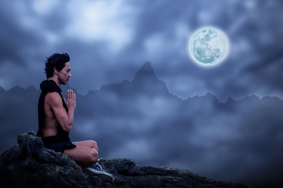 Man sitting meditating with mountains and the moon in the background